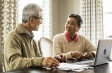 An older Asian couple sits down at the kitchen table to look at their insurance documents.