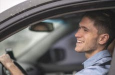 A young man in the driver's seat of his car smiling and enjoying life.