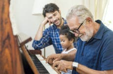 An old man sits with his son and granddaughter and plays on the piano.