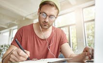 Young male college student doing paperwork while listening to music