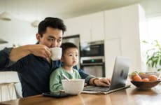 A father sits with his son in front of the laptop while sipping his coffee.