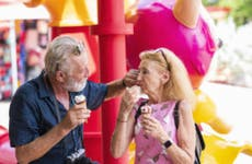 An older couple enjoys some ice cream at an amusement park.