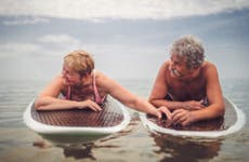 An older couple on surf boards holding hands on some calm water.