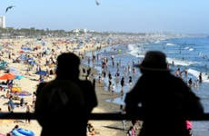 A couple looks over at a crowded beach in Santa Monica, California.