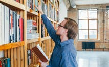 Student reaches for books in college library