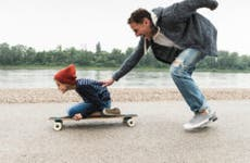 A father pushes his son along on a skateboard