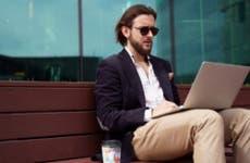 Man works on laptop outside