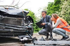 A woman crouches, wearing an orange vest and examining the damage to the front of her car while an insurance agent with a clipboard performs an inspection.