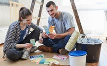 Two people look over paint colors in new home