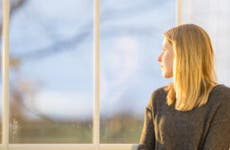 A woman sit and pensively stares out the window.