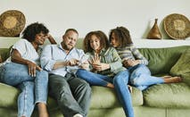 A father sits on the couch with his wife and two daughters, showing them something on his smartphone.