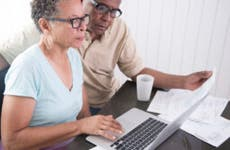 Couple using a laptop while sitting and looking at papers.