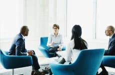 A group of executives meet with a financial expert in a meeting room with blue chairs and white walls. They are reviewing options for commercial insurance.