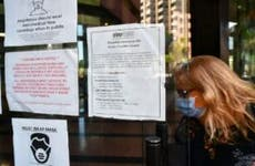 A woman wearing a facemask enters a building where the Employment Development Department has its offices in Los Angeles, California on May 4, 2020, past a posted sign mentioning the closure of the offices's public access counters due to the coronavirus pandemic. - Dismal US employment figures are expected with the release Friday May 8 of figures for April's US jobs report, with 30 million Americans filing for unemployment in the last six weeks.