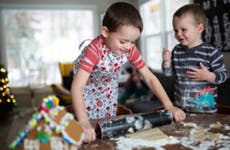 Two young brothers bake cookies together.