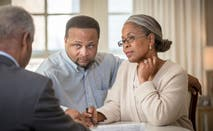A Black financial adviser speaks with a Black couple