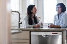A mother and daughter have a discussion in the kitchen