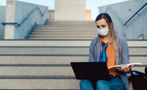Student works on laptop while wearing mask