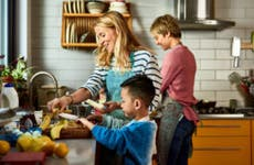 A same-sex couple does some cooking in the kitchen with their adopted Asian son.