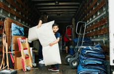 Young boy carries a pillow out of a moving truck.