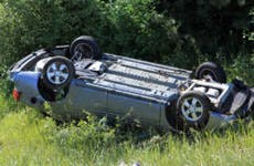 A shot of a gray car flipped over on its roof off the road after an accident.