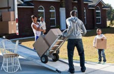 A Black family unloading a moving truck at a house in the suburbs.
