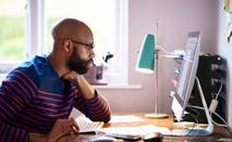 A Black entrepreneur looks over his computer