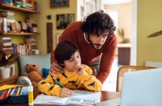 A father and young son looking at a computer, probably reading about mortgages.