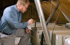 A home inspector assesses the attic in a home.