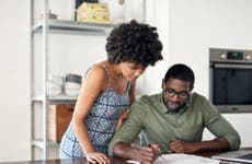 Black couple together in the kitchen at the table. The husband is sitting down while the wife is standing over him and looking at the papers on the table with him.