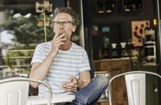 An older man with glasses sitting at a coffee shop outside and smoking a cigarette while he holds his smartphone.