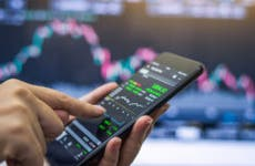 A trader holds a phone with a stock chart on it