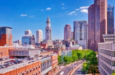 Shot of the cityscape of Boston Massachusetts with large buildings against a clear, blue sky.