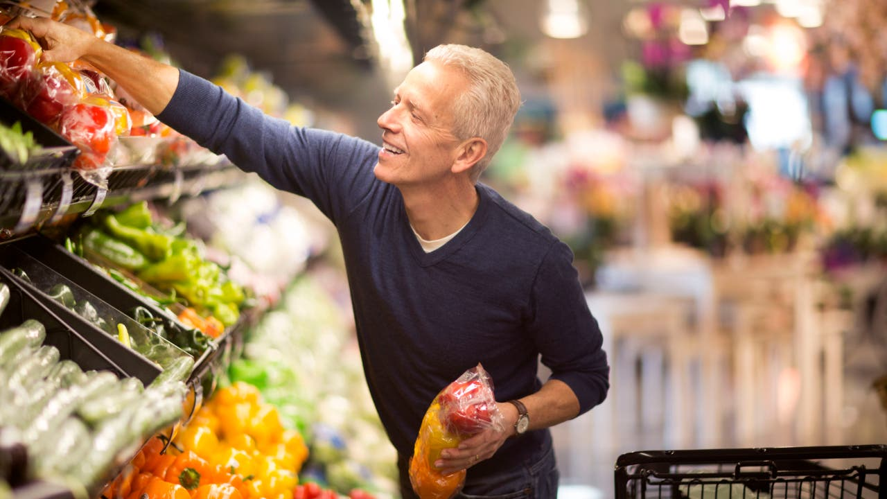 An old White man reaches for peppers in the produce department