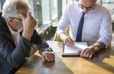 A man sits with his financial advisor looking over some documents.