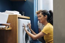 A woman and her husband are using a brand new washer machine.